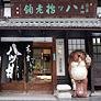 西尾八ッ橋の本店は、東大路通りと丸太町通りの交差点からひとすじ北の通りを東へ入ったところ。老舗ならではの古いたたずまいで、信楽焼のたぬきがお出迎えいたします。